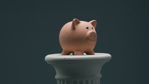 Confident businessman breaking a piggy bank with an hammer and pile of coins: deposit funds, investments and savings concept