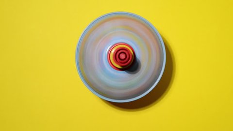 spinning top for children in action on a yellow background