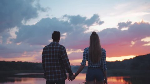 Back view of Young People in Love standing by the lakeside, Holding their Hands. Romantic atmosphere, relationship goals.