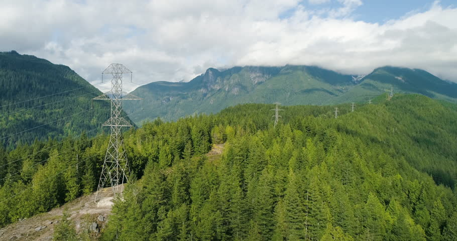 Power Towers Transmit Electricity To City Above Mountain Forest