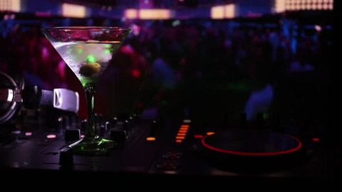 Glass with martini with olive inside on dj controller at nightclub. Dj Console with club drink at music party in nightclub with disco lights.