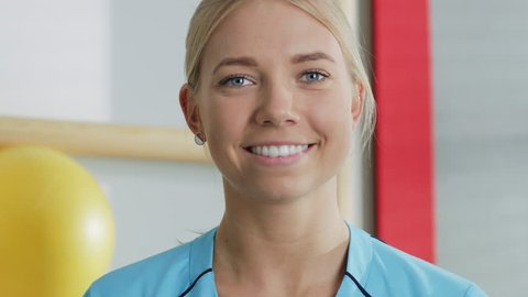 Portrait of Beautiful Young Professional Nurse / Physiotherapy Assistant Charmingly Smiles. Shot on RED EPIC-W 8K Helium Cinema Camera.