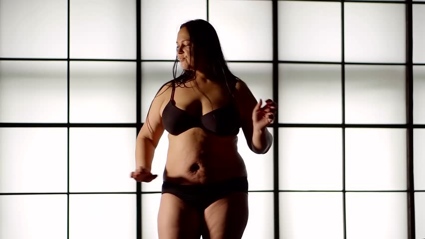 Very fat young girl with cellulite dancing on the background of a large window in her underwear | Shutterstock HD Video #1012080647