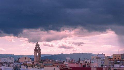 Belfry of St. Peter in Reus, Tarragona. Catalonia (Spain). Timelapse of dark storm clouds and rain