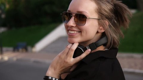 Traking footage of a young girl walking outdoors on the street or park. Cheerful and happy. Making a ponytail on her short fair hair, wearing sunglasses and put on the headphones