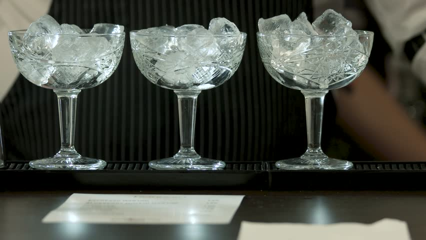 Row of glasses with ice cubes. Barman setting champagne goblets with ice.