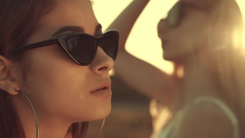 Four models on video. Tanned girl on the sand in sun.