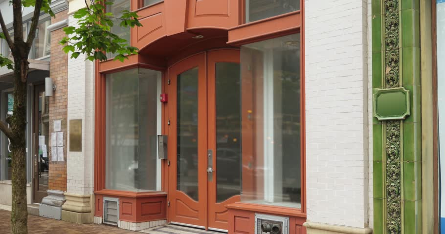 A daytime exterior (DX) establishing shot of an empty storefront or apartment building entrance in a city.   | Shutterstock HD Video #1012119347