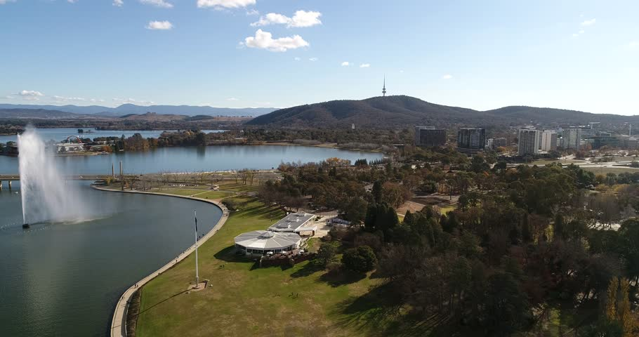 Water fountain and bridges across lake Burley Griffin in Canberra leading to parliament and government houses in federal district around capitol hill.