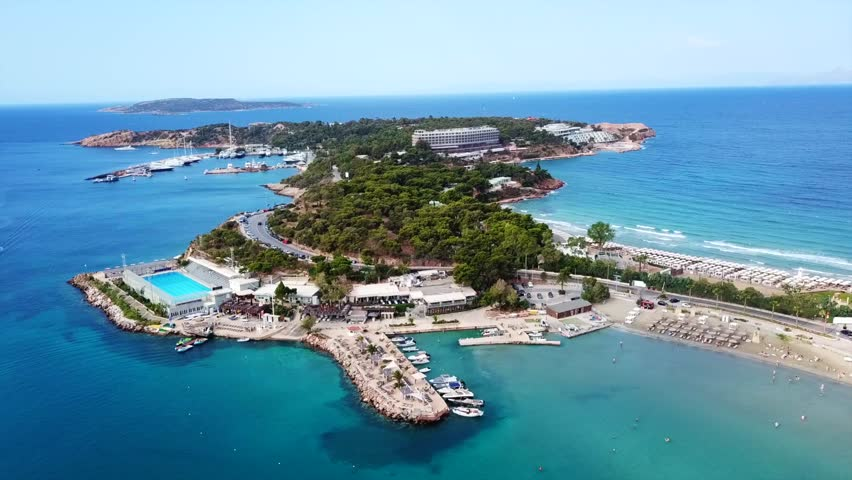 Aerial drone bird's eye video of famous celebrity area of Astir or Asteras in south Athens riviera Peninsula, Vouliagmeni, Greece