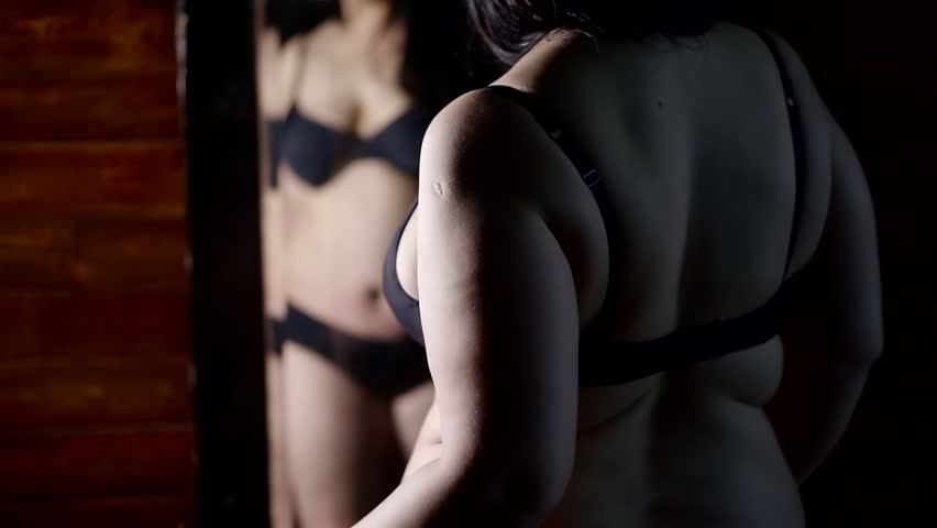 A fat woman in black lingerie with a big belly and pleats on her back looks at herself in the mirror. Close up