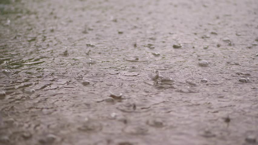 close-up, large, heavy drops of rain, rainfall, shower, fall with Water splashes, bubbles, on the wet surface of puddles, the surface of water. big drops from the rain on wet floor texture