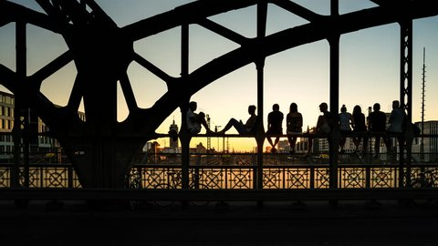 Munich Time Lapse, young people enjoying the sunset at cool insider spot on a railway bridge - 4k Time Lapse Video with day to night transition