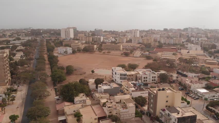 African city aerial with dirt football field: Dakar, Senegal.