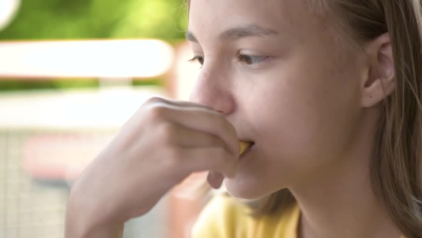 Young happy teenager eating tasty french fries in fast food restaurant. Teen  girl at fast food cafe with friends.