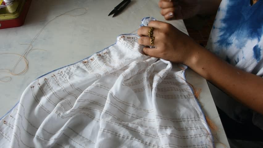 Thai woman people working batik tie dyeing natural color process fold bundle and sewing or arashi shibori on fabric at workshop in Nonthaburi, Thailand