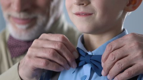 Grandfather adjusting grandson bow-tie, getting ready for concert, retro style