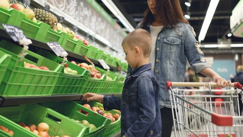 Adorable little boy is choosing apples in fruit and vegetables department in grocery store, his attractive mother is standing beside him and talking to her son.