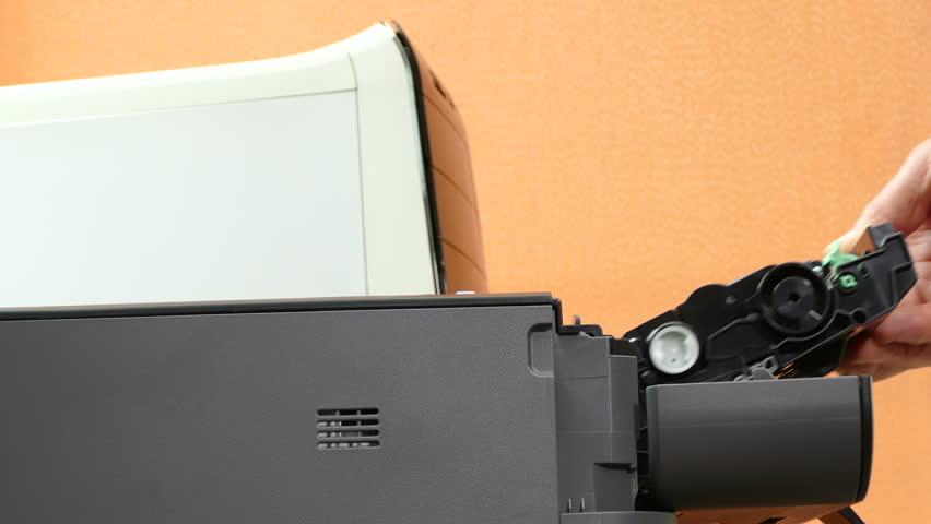 Closeup shot of a man's hand swapping the toner cartridge in a modern compact laser printer, alongside a desktop PC.