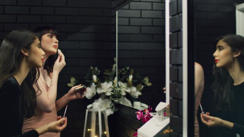 Two attractive women doing their makeup in front of a mirror. Shot with a RED camera. 4k footage.