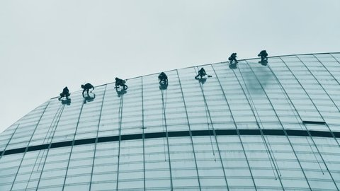 Skyscraper window cleaners. Several window cleaners on top a tall glass tower.