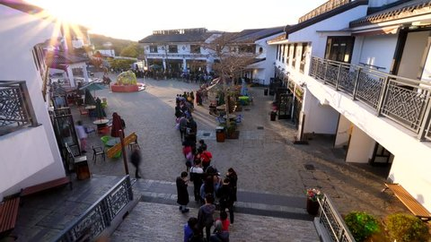 HONG KONG - MARCH 09, 2018: Long queue to Ngong Ping 360 cable car, unidentified people stay in line at village square, wide angle time lapse shot from above. Evening time, tourists want travel back