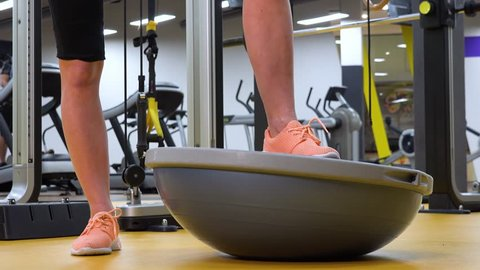 A fit woman tries a bosu ball with her leg in a gym - closeup