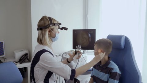 Doctor examine ear of little boy with ENT telescope