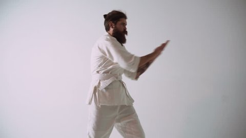Bearded man in kimono shows funny karate gestures.Funny handsome man fighting against an imaginary opponent with awkward clumsy moves.