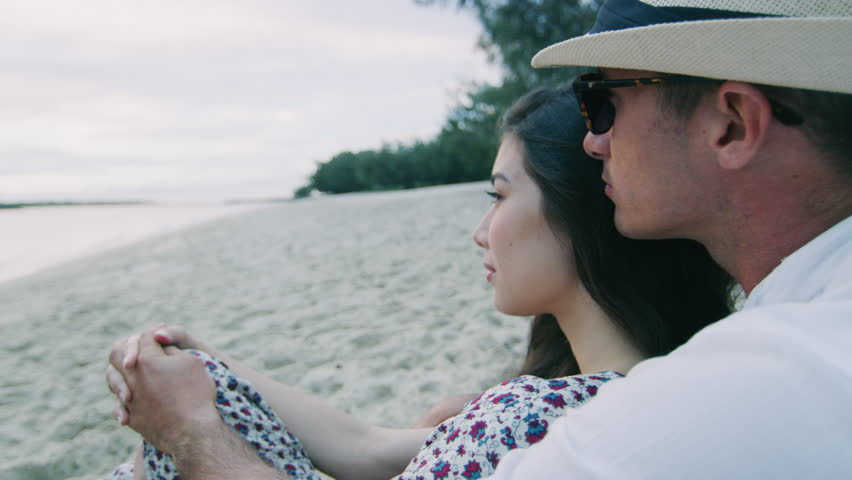 Close up of handsome guy and beautiful girl sitting on beach and looking out at ocean at sunset. Shot with a RED camera. 4k footage.