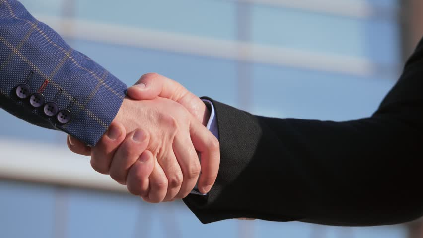 Close-up of handshake of businessmen outdoors. Two businesspeople shaking hands and greeting in slow motion