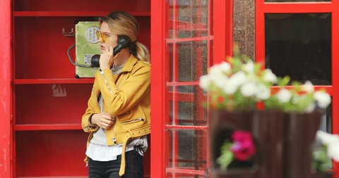 fashionable hipster girl smiling talking on phone using public payphone system old-fashioned telephone booth red call box for telecommunication