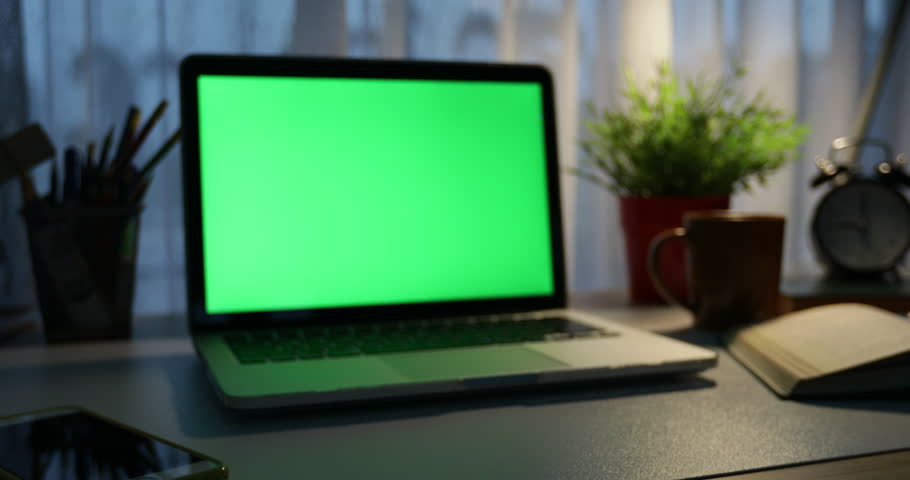 Laptop with green screen. Dark office. Dolly in . Perfect to put your own image or video.Green screen of technology being used. Chroma Key laptop | Shutterstock HD Video #1012335227