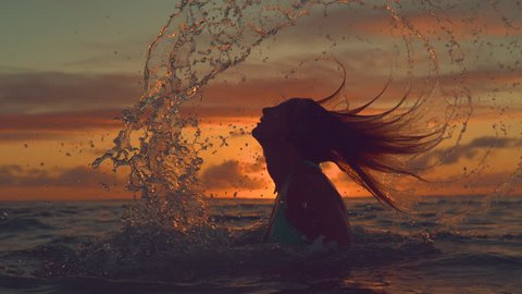 SLOW MOTION, CLOSE UP, SILHOUETTE: Playful girl splashes refreshing sea water with her long hair on a spectacular summer evening near tropical island. Amazing shot of woman flipping her hair back.