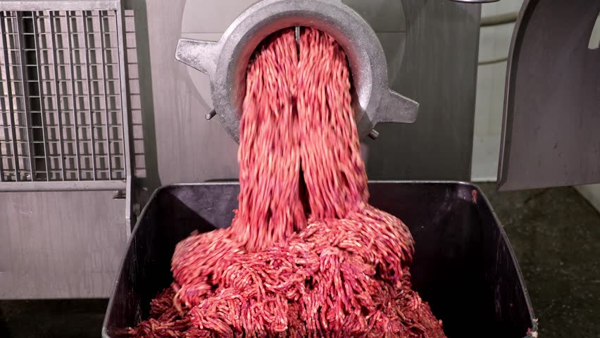 Processing lard or meat in minced meat on a huge meat grinder at a meat factory closeup. | Shutterstock HD Video #1012344137