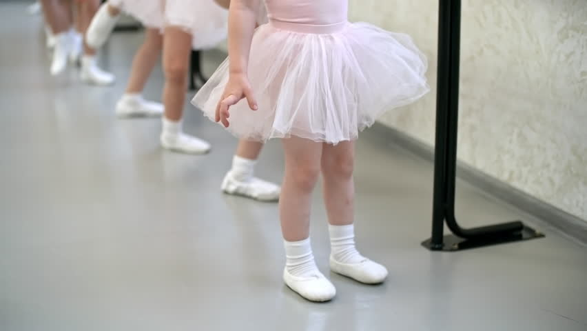 Tilt up shot of group of little girls in ballet clothes standing at ballet barre and stretching legs for split, their female teacher helping them