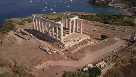 Athens Greek temple of Poseidon in morning light. Aerial drone view. Blue ocean and sailing boats in background. Cape Sounion one of the major monuments of the Golden Age of Athen.