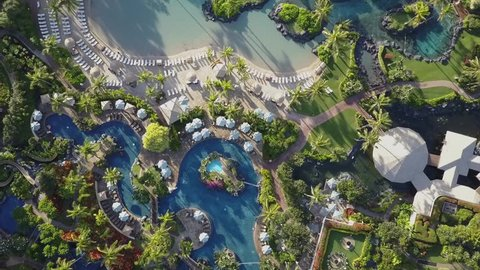 Grand Hyatt Kauai Luxury Hotel Resort top down overhead aerial 4k view by drone. Palm trees, Sunshade, parasol, hot tub. water slide. Pools, garden, shoreline and beach from above.