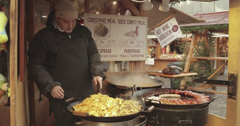 Tallinn, Estonia - December 22, 2017: Man frying potatoes and sausages - a traditional Christmas dish of street food on streets of Europe in winter during the Christmas holidays