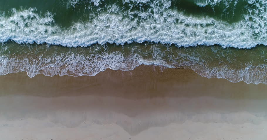 Beautiful 4K tropical beach aerial - a bird's eye view of ocean waves crashing against an empty beach from above | Shutterstock HD Video #1012392017