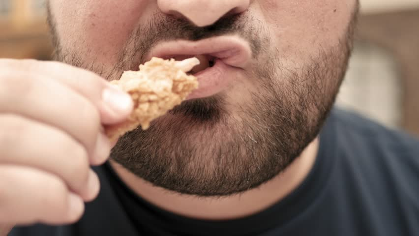 Fat man eats chicken nuggets, harmful and tasty fast food, close up