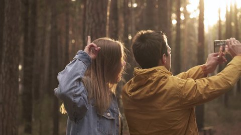 Young couple making selfie at smartphone at background of sunny green forest. Hiking emotionally concept of travelers spending weekend in wild side. Enjoyment, friendly moments, funny time outdoor