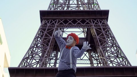 Mime in stripped shirt playing on invisible violin near Eiffel tower