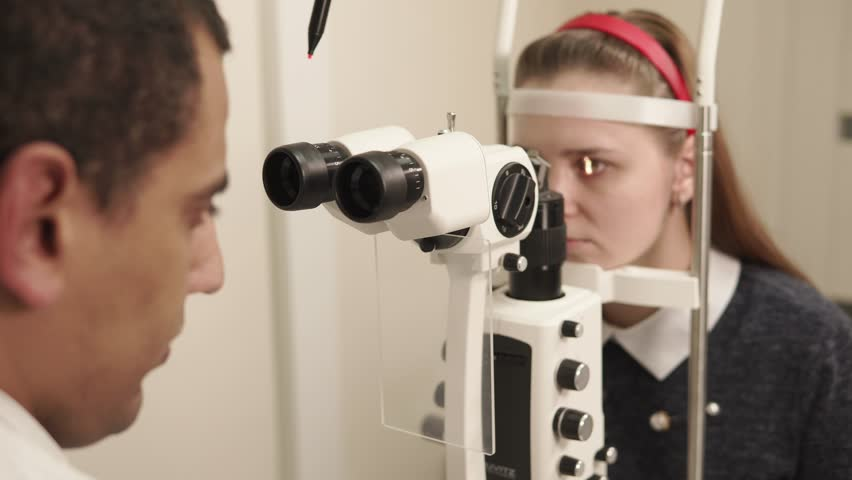 the oculist doctor works in a private clinic, the man uses an apparatus for biomicroscopy of the eye to check the sight of an adult teenager #1012445177
