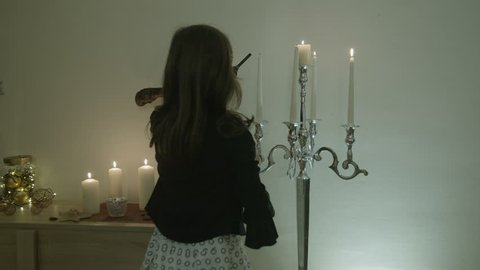 Young girl lighting a candles for celebration.Interior of beautiful living room decorated for Christmas / New Year.