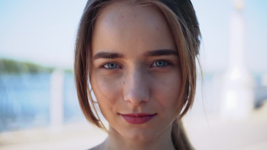 Nice Ukrainian girl with blue eyes looking directly at camera, smiling. Guy making fun of lovely girl, put ice cream on nose. Laughing. Outdoors.   Shutterstock HD Video #1012468187