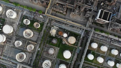 Aerial top down view over oil refinery or chemical factory and power plant with many storage tanks and pipelines. Shot with 4K UHD resolution drone.