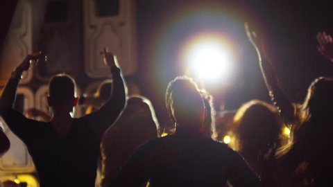 Medium shot of unrecognizable young people swaying hands to rhythmic music when partying in nightclub