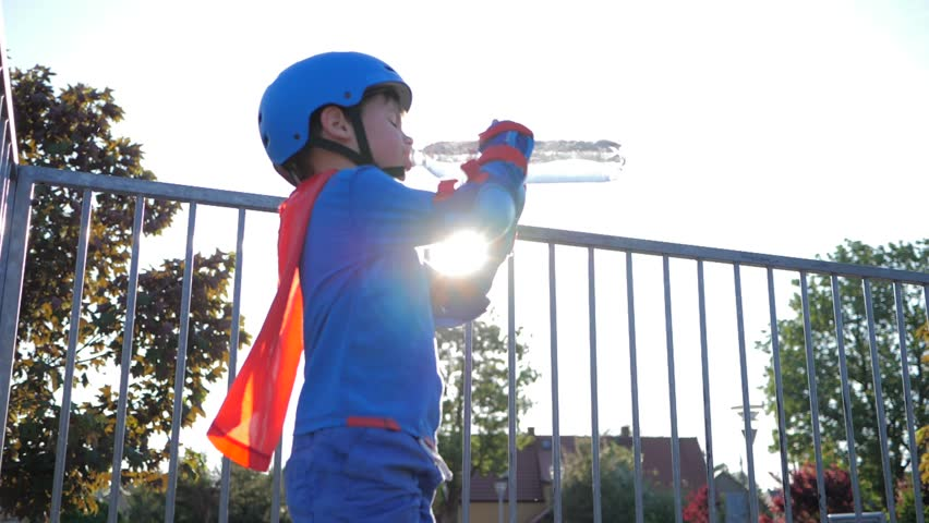 sport children drinking water, boy into superhero costume with cooling beverage in plastic container on open air in backlight close-up