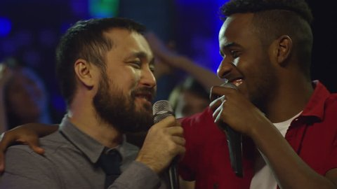 Medium shot of two young male friends of different ethnicities embracing  each other when singing into microphone in karaoke bar during party